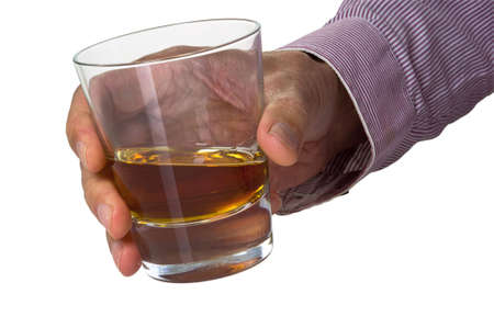 Glass from whisky in a palm of the man on a light background