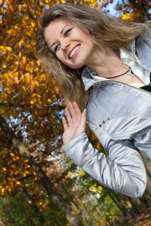 young woman blonde on a background trees in a park