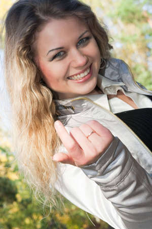 The young blonde calls hand gesture
