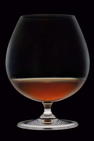 Glass with alcohol against a dark background