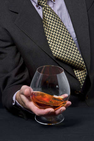intoxicant: The man holds in a hand a glass with alcohol against a dark suit