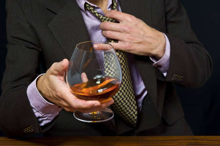 Glass with alcohol in a hand of the man in a suit on a light background
