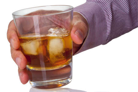The hand holds a glass with alcohol on a white background