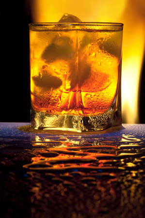 Glass with alcohol against fire with reflexion, in a glass ice. Against a dark background.