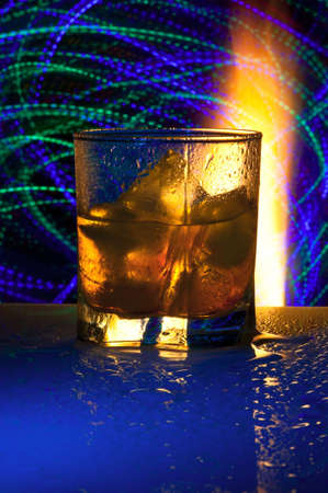 Glass with alcohol against fire with reflexion, in a glass ice. Against a dark background with colour small lamps.
