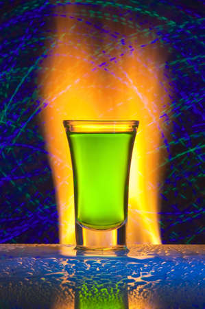 Glass with alcohol against fire with reflexion. Against a dark background with colour small lamps.