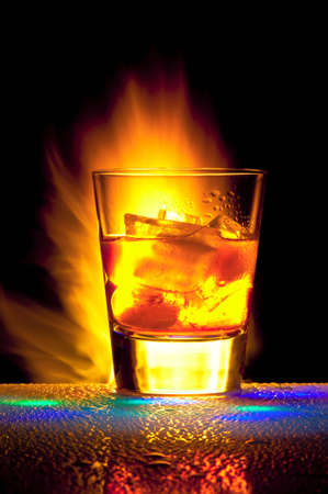 Glass with alcohol against Bengal fires with reflexion, in a glass ice. Against a dark background