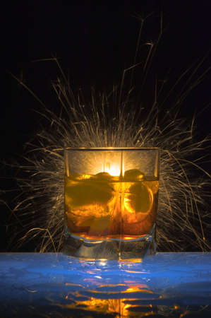 Glass with alcohol against Bengal fires with reflexion, in a glass ice. Against a dark background with colour small lamps.