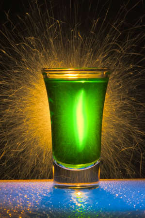 wine stocks: The wine-glass for a cocktail with alcohol of green colour against Bengal fires with reflexion