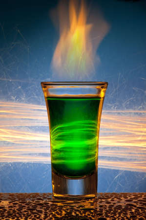 The wine-glass for a cocktail with alcohol of green colour against Bengal fires with reflexion, in a glass burns fire. Stok Fotoğraf