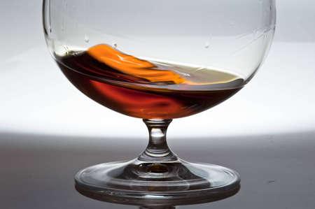 Glass with cognac against from white to the dark. A liquid in a glass ïåðåòèêàåò here and there Stok Fotoğraf