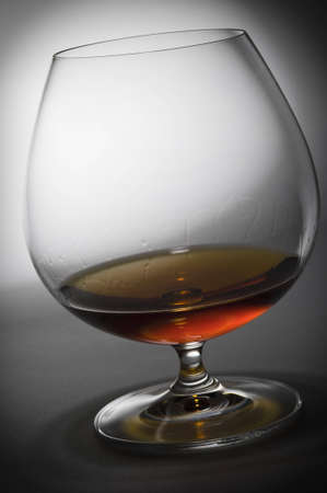 Glass with cognac against from white to the dark. Cognac drops flow down on glass walls. Stok Fotoğraf