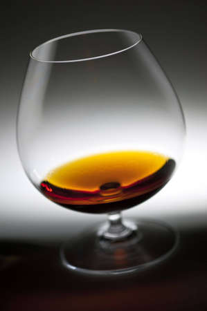 against the flow: Glass with cognac against from white to the dark. Cognac drops flow down on glass walls. Stock Photo