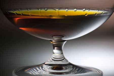 Cognac drops flow down on glass walls. Cognac is shone through a glass