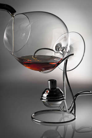 The glass with alcohol costs on a support for heating. The drink joins it. Stok Fotoğraf