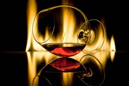 intoxicant: Il vetro con il cognac si trova orizzontalmente contro gli incendi con riflessione contro uno sfondo scuro