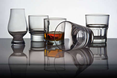 Play of light and colours in glasses for whisky with reflexion. One glass lies on one side in another whisky is poured.