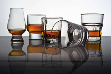 Play of light and colours in glasses for whisky with reflexion. One glass lies on one side in others whisky is poured.