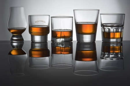 Five glasses from whisky stand on glass and are reflected in it