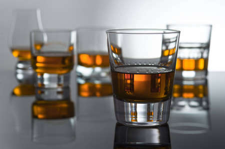 Play of light and colours in glasses for whisky with reflexion. One glass in the foreground the others in it is washed away not the sharp.