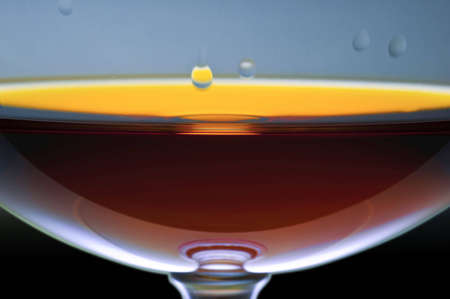 Play of light and colours in a glass with alcohol. Alcohol drops on glass walls