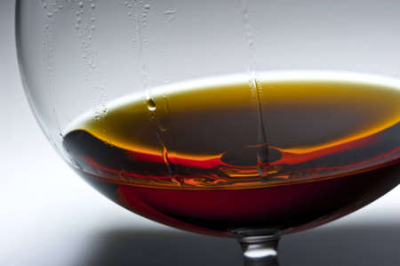 Detailed shooting of a glass with alcohol on a gleam, liquid drops flow down on glass walls Stok Fotoğraf