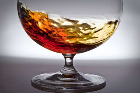 Raging liquid of alcohol of orange colour in a glass on a grey background