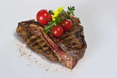 Meat piece on a white plate with tomatoes and green salad