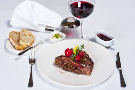 Meat piece on a white plate with tomatoes and green salad.On a table at restaurant it is served with a red wine glass Stok Fotoğraf