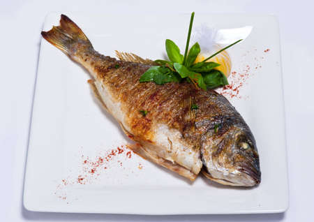 Fried fish is prepared at restaurant on a white plate.Tablewares on each side Stok Fotoğraf