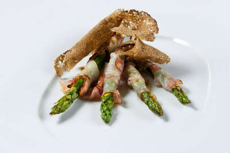 entree: dish from bread of asparagus of bacon on a white background Stock Photo