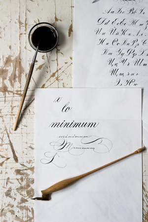 Word Calligraphy written on paper, with calligraphy tools in background