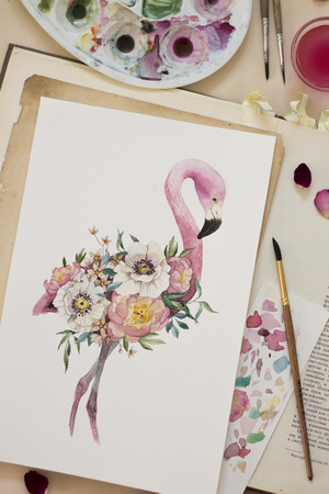 Workspace. Exotic flowers and flamingo painted with watercolor, paintbrush, candles and bottles isolated on white background. Overhead view. Flat lay, top view