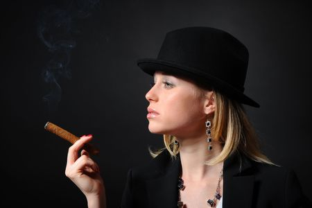 Portrait of the beautiful girl in a hat smoking a cigar photo