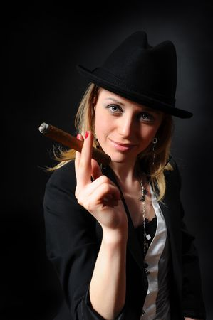 Girl in a hat with a cigar in a hand on a black background Stock Photo - 6820514