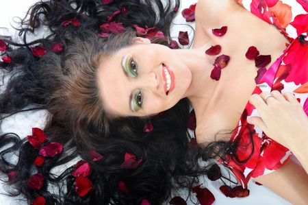 Close-up the smiling young girl lies in petals of roses photo