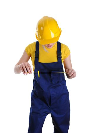 Girl the builder in a yellow helmet and building overalls looks at a roulette.Isolated on white background  photo