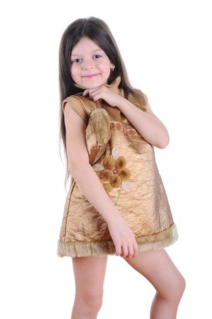 Little girl in a gold dress puts on her shoulder a small gold purse.  Isolated on white background Stock Photo - 6820493