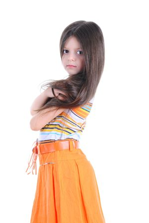 Long-haired girl in an orange skirt, standing with her arms folded on his chest.  Isolated on white background photo