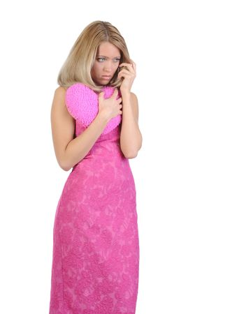 Sad girl in a pink dress embracing a heart with his hands. Isolated on white background photo