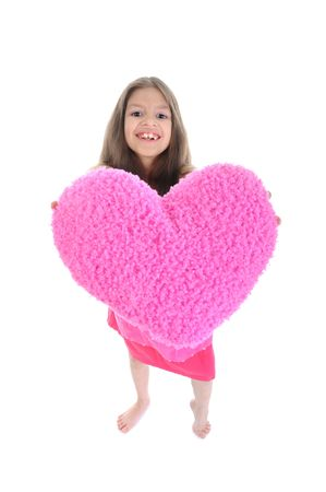 The little girl in a pink heart holds in his hands. Isolated on white background photo