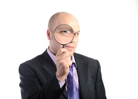 funny glasses: Businessman in a suit looking through a magnifying glass. Isolated on white background