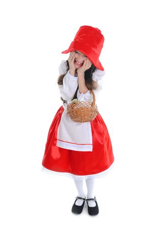 Happy girl in a red cap with a basket holding his face. Isolated on white background photo