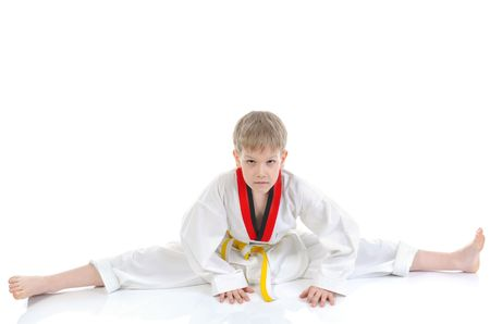 Junior karate in the position of spagat. Isolated on white background photo
