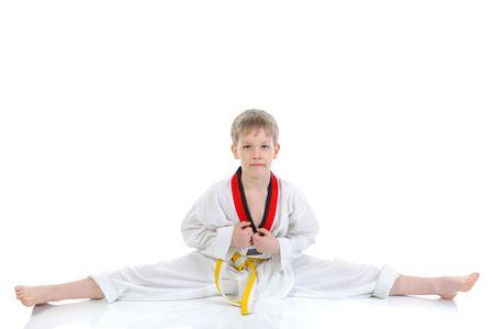 kimono: Estudiante de j�venes de artes marciales, sentado en el spagat. Aislados en fondo blanco