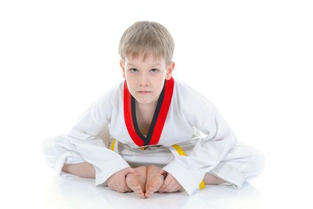 The boy in a kimono sits on a floor. isolated on a white background photo