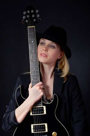 Beautiful blonde girl in a black hat holding a guitar in his hands photo