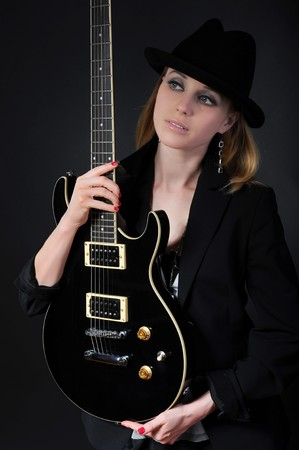 Blonde in a black hat and jacket with guitar in hand photo