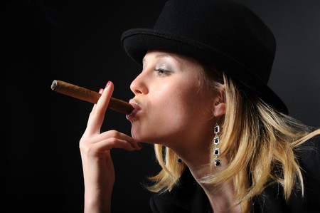 Portrait of a beautiful girl with a cigar on a black background photo