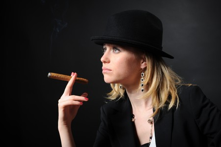 Beautiful girl in a hat with a cigar on a black background photo
